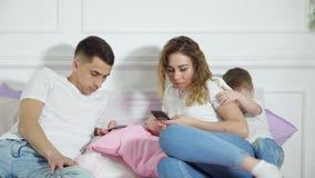 De ouders kijken in hun mobiele telefoons bestedend geen aandacht aan hun kind Vlucht van werkelijkheid, afhankelijkheid van stock videobeelden