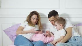 De ouders kijken in hun mobiele telefoons bestedend geen aandacht aan hun kind Vlucht van werkelijkheid, afhankelijkheid van stock video