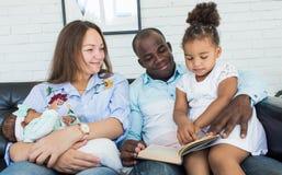 De ouders lezen een boek aan kinderen die op de laag zitten Gelukkige multi-etnische familie Familiewaarden royalty-vrije stock afbeelding