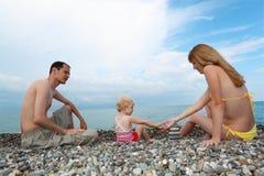 De ouders met kind op overzeese kust bouwen piramide royalty-vrije stock foto