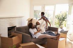De ouders nemen een Onderbreking op Sofa With Son On Moving-Dag stock afbeelding