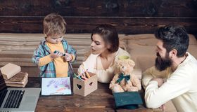 De ouders onderwijst zoon, houten muurachtergrond Jongen die aan mamma en papa met aandacht luisteren Homeschoolingsconcept ouder stock afbeelding
