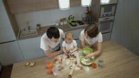 De ouders samen met een kleine dochter koken thuis in de keuken Het concept familiegeluk stock footage