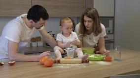De ouders samen met een kleine dochter koken thuis in de keuken Het concept familiegeluk stock videobeelden