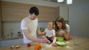 De ouders samen met een kleine dochter koken thuis in de keuken Het concept familiegeluk stock video