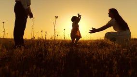 De ouders worden onderwezen om klein kind te lopen, maakt het meisje haar eerste stappen in de zon, langzame motie stock footage
