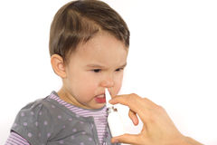 De oudershand van een meisje past een neus geïsoleerde nevel toe Stock Afbeelding