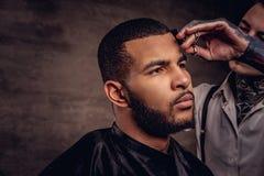 De ouderwetse professionele getatoeeerde kapper doet een kapsel aan een Afrikaanse Amerikaanse cliënt op donkere geweven royalty-vrije stock foto's