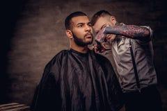 De ouderwetse professionele getatoeeerde kapper doet een kapsel aan een Afrikaanse Amerikaanse cliënt op donkere geweven stock foto