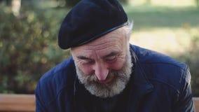 De oudste in hoed rust op de bank van het park en begroet met glimlach op gezicht aan voorbijgangers stock footage