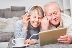 De oudsten luisteren aan muziek met plezier stock foto