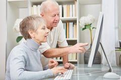 De oudsten met computer leren over Internet stock afbeelding