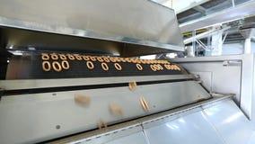 De output van de gebeëindigde ongezuurde broodjes op een transportband stock videobeelden