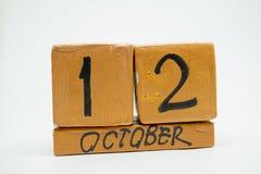 12 de outubro Dia 12 do mês, calendário de madeira feito a mão isolado no fundo branco mês do outono, dia do conceito do ano imagem de stock