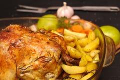de oven-gebakken knapperige korst vulde kip op een plaat met aardappels, appelen, knoflook stock afbeelding