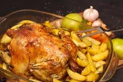 de oven-gebakken knapperige korst vulde kip op een plaat met aardappels, appelen, knoflook stock foto's