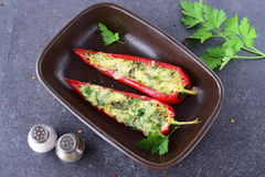 De oven kookte rode die paprika met kaas, knoflook en kruiden in een ceramische vorm op een abstracte grijze achtergrond wordt ge Stock Afbeelding