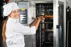 De Oven van chef-kokplacing pizza in Stock Afbeelding