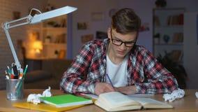 De overbelaste agressieve student die boeken van lijst werpen, kan geen taak oplossen stock video