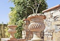 De overladen potten van de bloemklei kenmerken steenmuur Stock Foto's