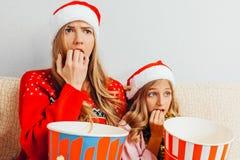 De overweldigde moeder en haar weinig dochter, kleedden zich in Santa Claus h royalty-vrije stock afbeelding