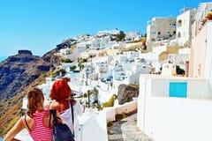 De overweldigde toeristenvrouwen ontdekken Santorini-schoonheid Griekenland stock afbeelding