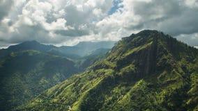 De overweldigende tijdtijdspanne van groene bergen als wolken beweegt zich om hen in zonlicht te baden stock footage