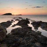 De overweldigende zonsopgang van de landschapsdageraad met rotsachtige kustlijn en lang exp Stock Afbeeldingen