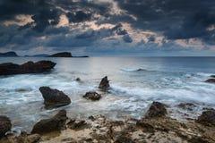 De overweldigende zonsopgang van de landschapsdageraad met rotsachtige kustlijn en lang exp Stock Afbeelding
