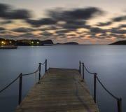 De overweldigende zonsopgang van de landschapsdageraad over pier en lange blootstellingsmed Stock Fotografie