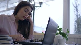 De overwerkte vermoeide computertechnologie en de boeken van het studenten vrouwelijke gebruik moderne aan studie van online curs stock footage