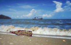 De overzeese eikelkolonie op een bruine gedumpte glasfles verontreinigt bij het zandstrand, de vage plons van overzeese golf en d stock foto
