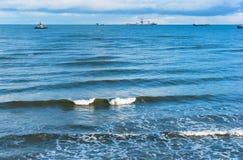 De overzeese golf, stormt op zee, golven op zee omwikkelend op de kust, vrachtschip Stock Foto