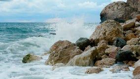 De overzeese golven breken op een rotsachtige kust stock video