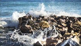 De overzeese golven breken de stenen royalty-vrije stock afbeeldingen