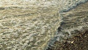 De overzeese golven met schuim slaan tegen de steenachtige kust stock footage
