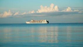 De overzeese golven op het strand sluiten omhoog, op de horizon een schip zwemt
