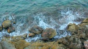 De overzeese golven raken de rotsen stock footage