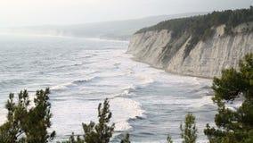 De overzeese golven slaan op de rotsachtige kust stock video