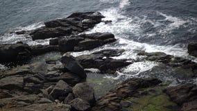 De overzeese golven verdelen tegen granietrotsen, een onweer stock footage