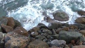 De overzeese golven zijn over de stenen stock footage