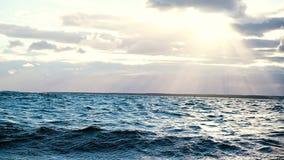De overzeese golven zijn woedend tegen de achtergrond van zonlicht bij zonsondergang, langzame motie Rimpelingen en plonsen van d stock footage