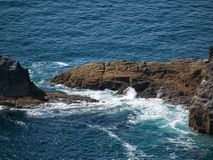 De overzeese onderbrekingen bij de bruine rots in de Atlantische Oceaan stock fotografie