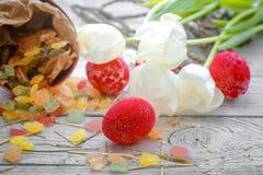 De Pâques toujours la vie avec des oeufs de sucrerie et des tulipes blanches Images libres de droits