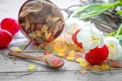 De Pâques toujours la vie avec des oeufs de sucrerie et des tulipes blanches Image stock