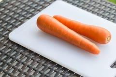 Is de paar lange verse ruwe wortel op een plastic scherpe raad witte kleur Royalty-vrije Stock Foto