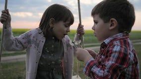 De paardebloem van de kindslag, de gelukkige jong geitjejongen en de meisjestweelingen die in blowballbloem blazen, mooie glimlac stock footage