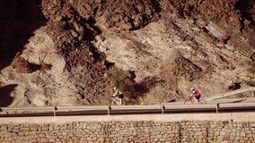 De paarfietsers berijden neer op bergenweg royalty-vrije stock fotografie