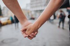 De paarhanden sloten samen in openlucht in liefde en romantische verhouding Sluit omhoog lichaam Man en vrouw in de stad stock foto's