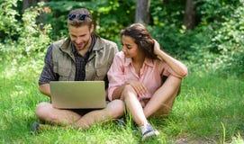 De paarjeugd besteedt in openlucht vrije tijd met laptop De moderne technologieën bieden de kans online te zijn en het werk in om stock afbeelding